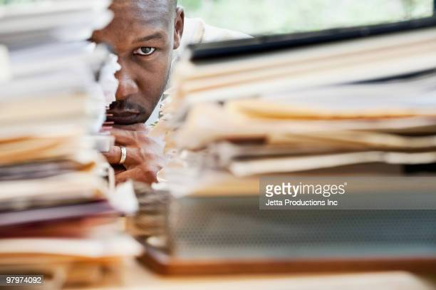 african businessman hiding behind stack of paperwork - burden stock pictures, royalty-free photos & images