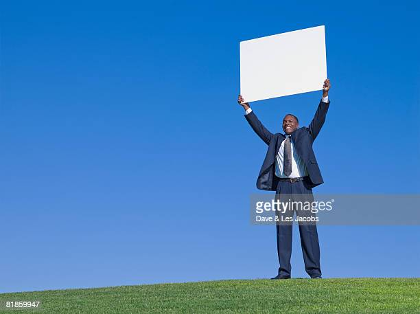 African businessman holding blank sign