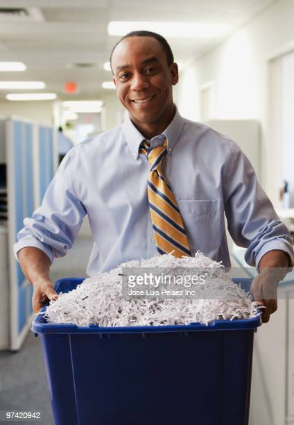 African businessman holding shredded paper for recycling