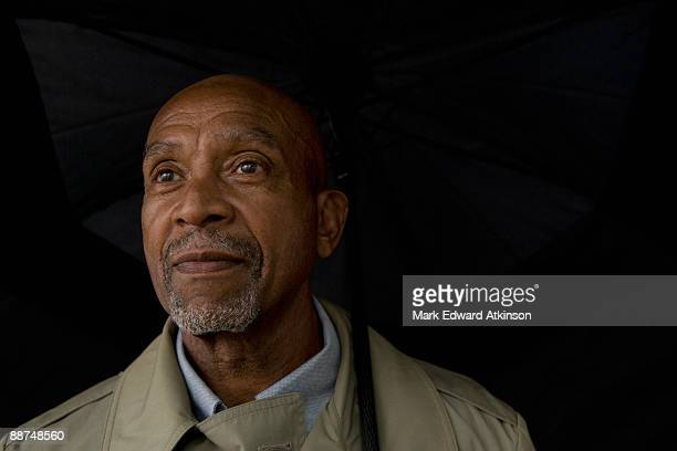 african businessman holding umbrella - 65 69 jaar stockfoto's en -beelden