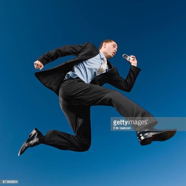 African businessman in mid-air holding cell phone