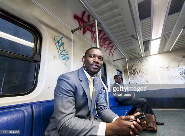 African businessman in the train listening to music