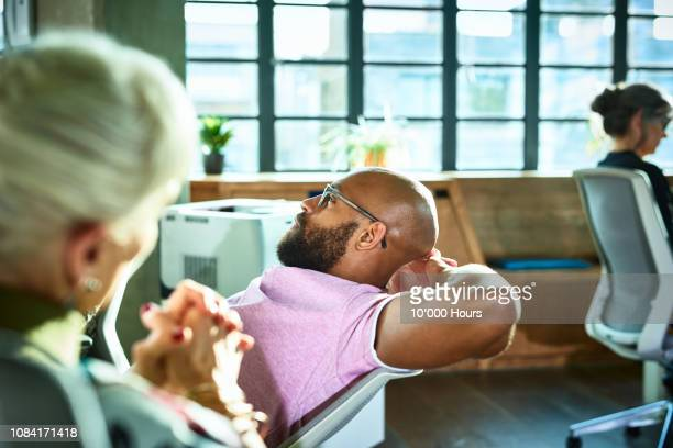 African businessman leaning back on office chair with hands behind head