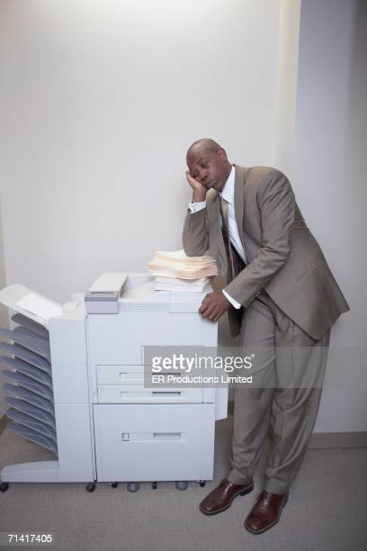 African businessman leaning on copier
