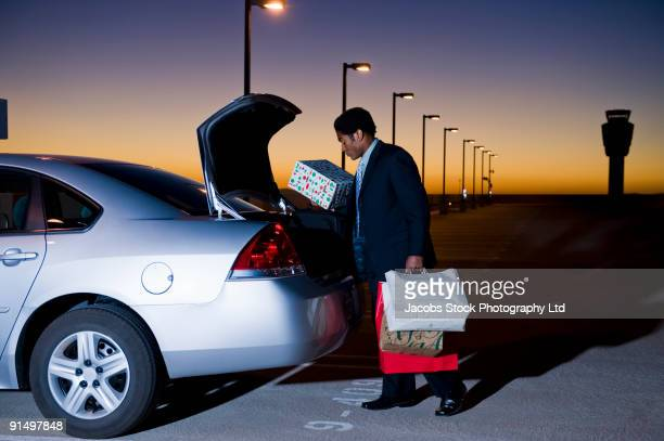 African businessman loading packages into car in parking lot