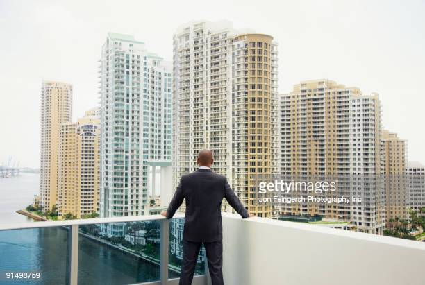 African businessman looking at city from urban balcony