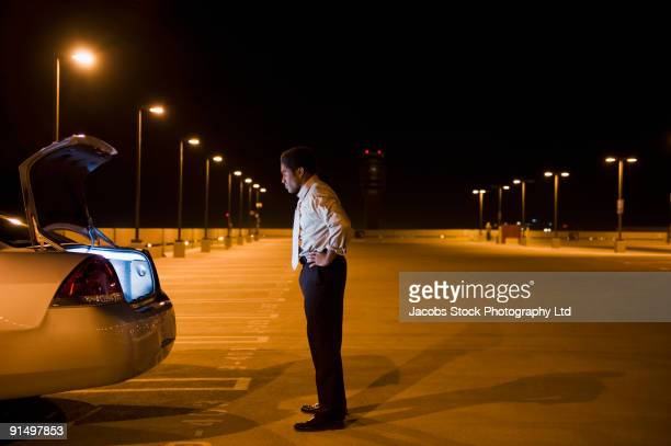 African businessman looking into glowing car trunk in parking lot