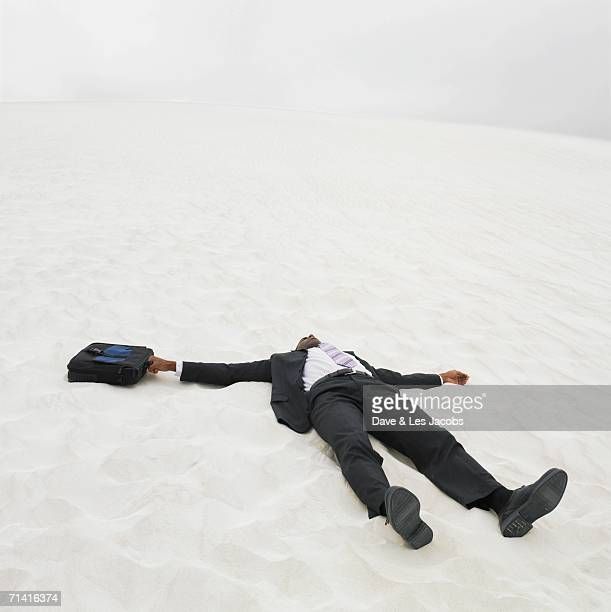 African businessman lying in the sand