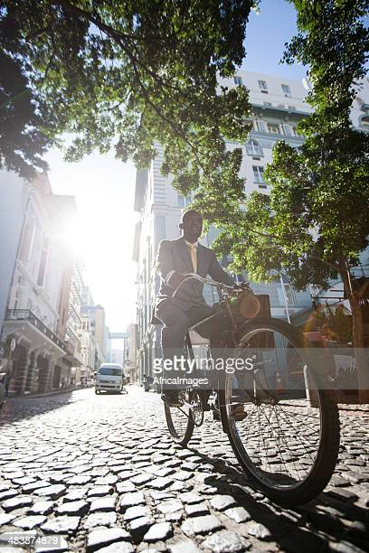 African businessman on his bicycle commuting Greenmarket Square.