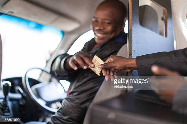 african businessman paying the taxi driver - south african currency stock photos and pictures