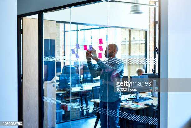 african businessman placing sticky notes on glass partition - black man bulge stock pictures, royalty-free photos & images