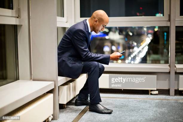 African businessman reading text message on his mobile phone