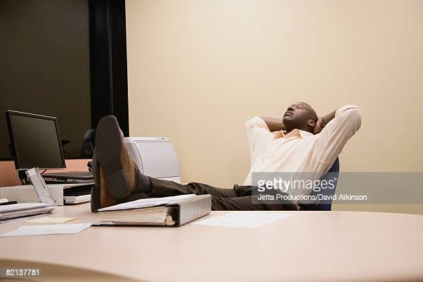 african businessman relaxing with feet on desk - zurücklehnen stock-fotos und bilder