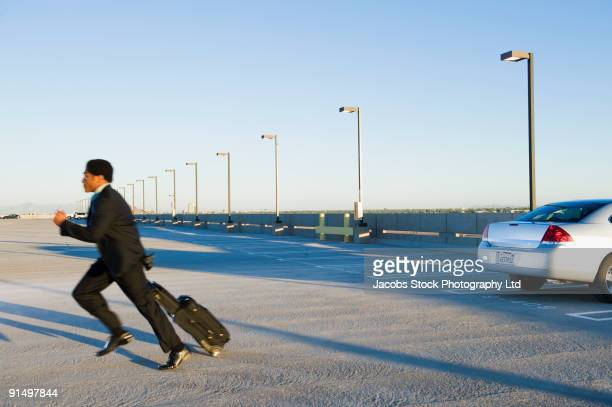 African businessman running to catch plane at airport