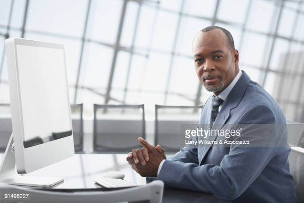 african businessman sitting at conference table - 会長 ストックフォトと画像