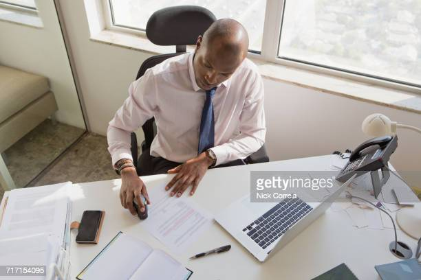 African businessman stamping document at the office