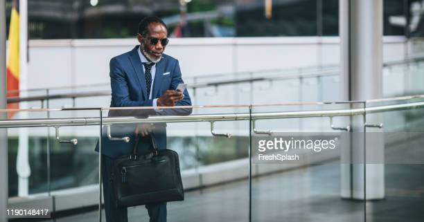 african businessman standing on a balcony - ambassador stock pictures, royalty-free photos & images