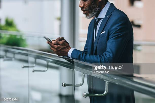 african businessman standing outdoors and typing on a cell phone - economist stock pictures, royalty-free photos & images