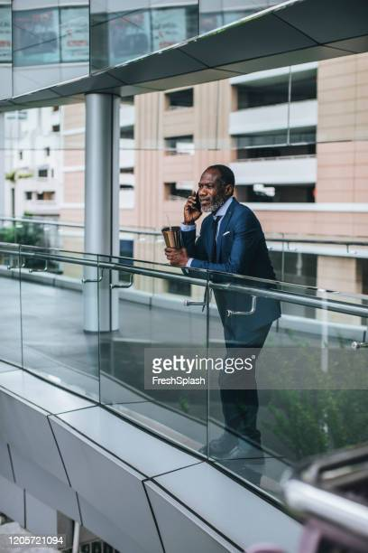 african businessman talking on his cell phone - ambassador stock pictures, royalty-free photos & images