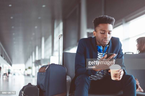 African businessman using cell phone at airport