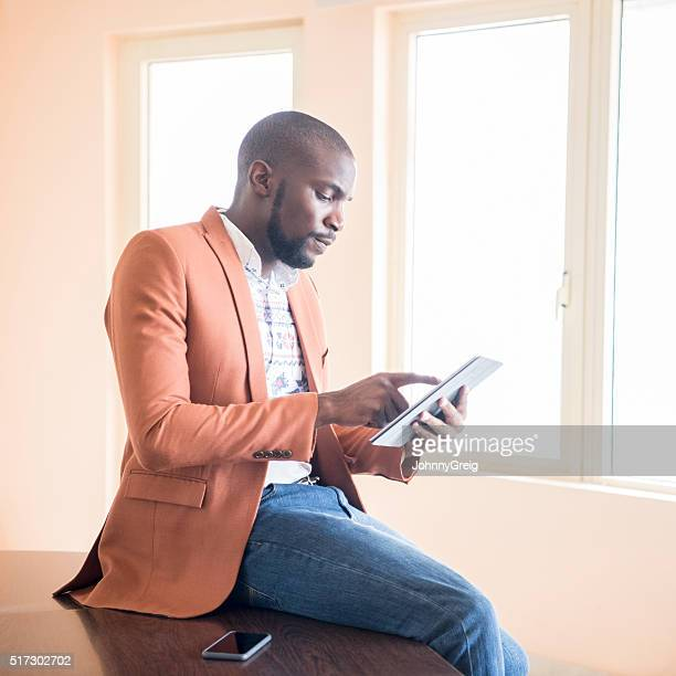 African businessman using digital tablet indoors