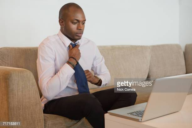 African businessman using laptop and adjusting his tie