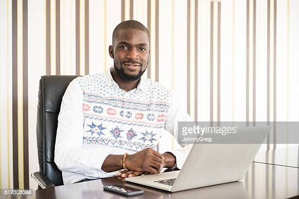 African businessman using laptop in modern office