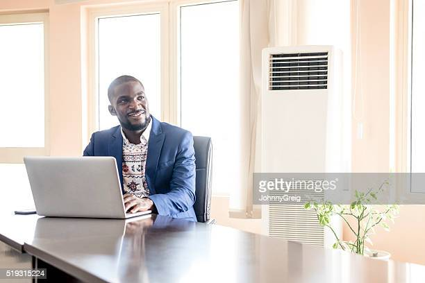 African businessman using laptop looking away, smiling