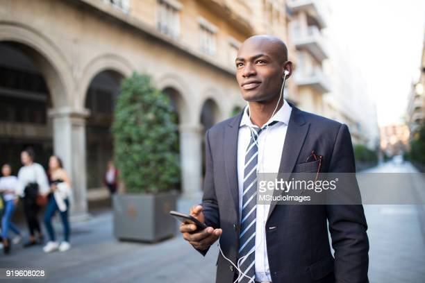 african businessman using mobile phone - nigerian men stock photos and pictures