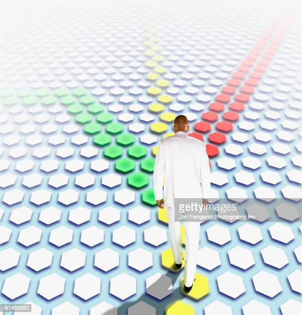 African businessman walking along colored path of hexagons