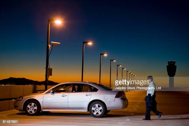 African businessman walking to car in parking lot
