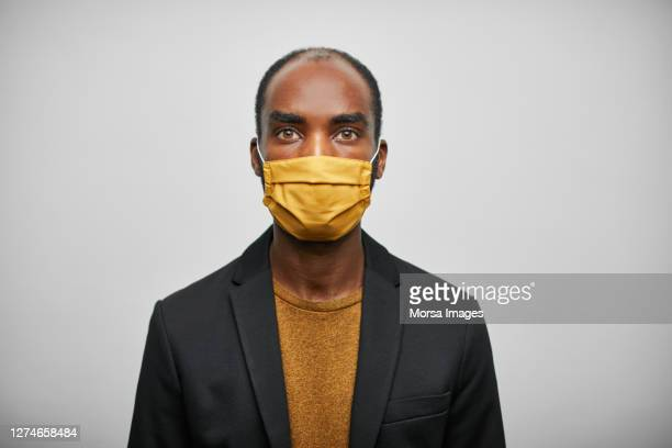 african businessman wearing home made face mask on white background - veste noire photos et images de collection