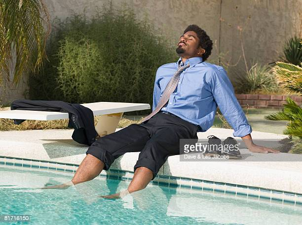 african businessman with feet in swimming pool - barefoot black men stock pictures, royalty-free photos & images
