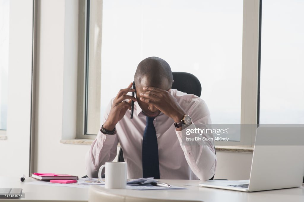 African businessman with head in hand at the office : Stock Photo