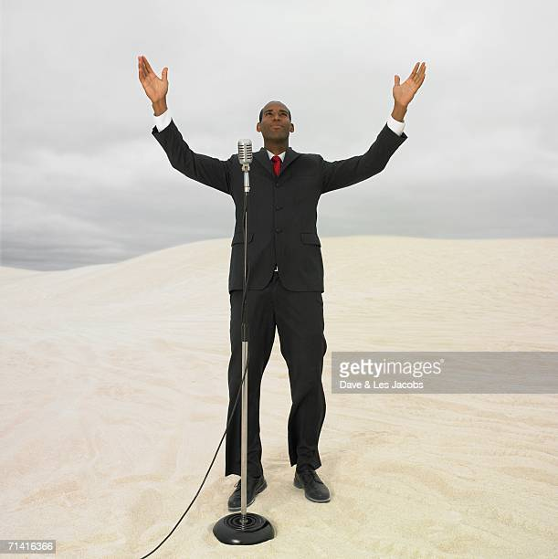 african businessman with microphone in desert - 説教師 ストックフォトと画像