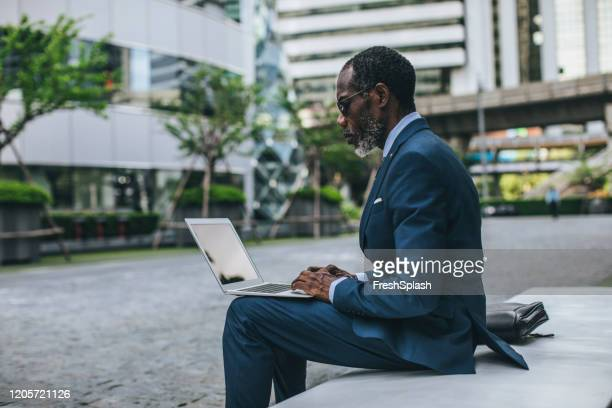 african businessman working outdoors - economist stock pictures, royalty-free photos & images