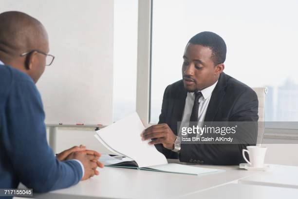 african businessmen discussing at the office - nigerian men stock photos and pictures