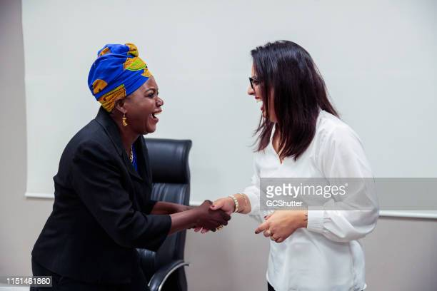 african businesswoman and an indian girl shaking hand while laughing loud - expatriate stock pictures, royalty-free photos & images