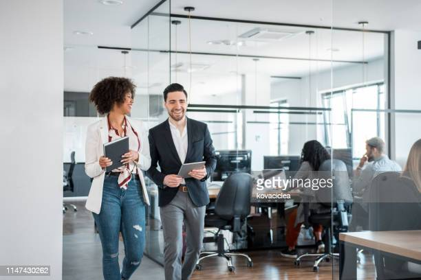 african businesswoman and her caucasian coworkers using digital tablet and walking in the office - business casual stock pictures, royalty-free photos & images