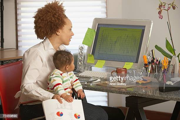 african businesswoman at computer with baby on lap - black ginger baby stock photos and pictures