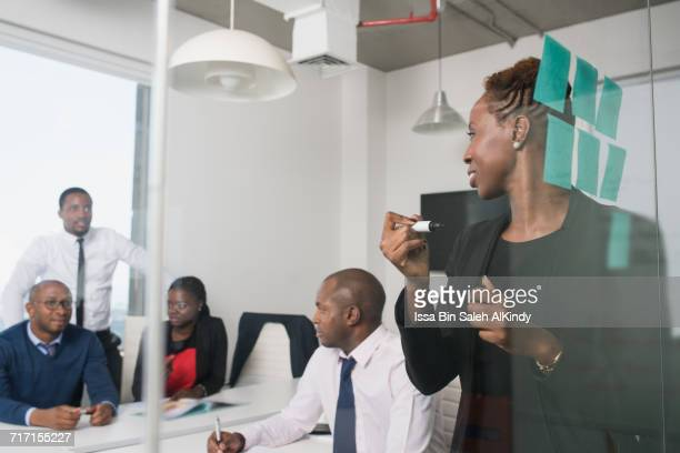 African businesswoman discussing project with colleagues in office