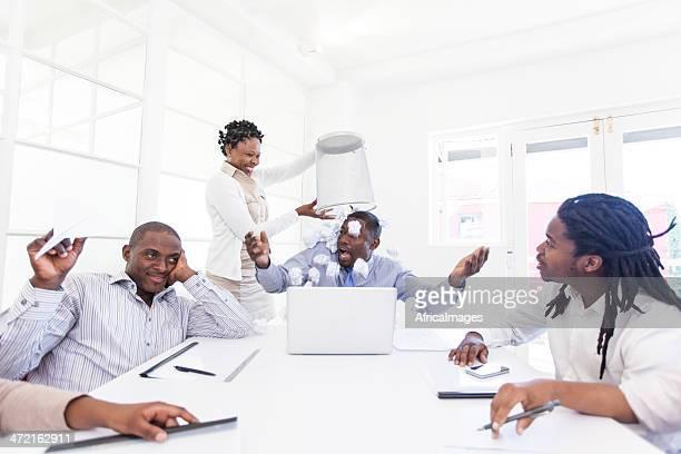 Afrikanische Geschäftsfrau emptying ein bin über Ihre Geschäftspartner head