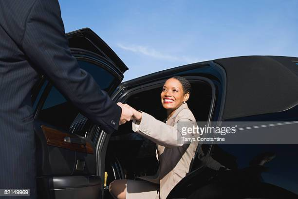 african businesswoman getting out of limousine - limousine stock pictures, royalty-free photos & images