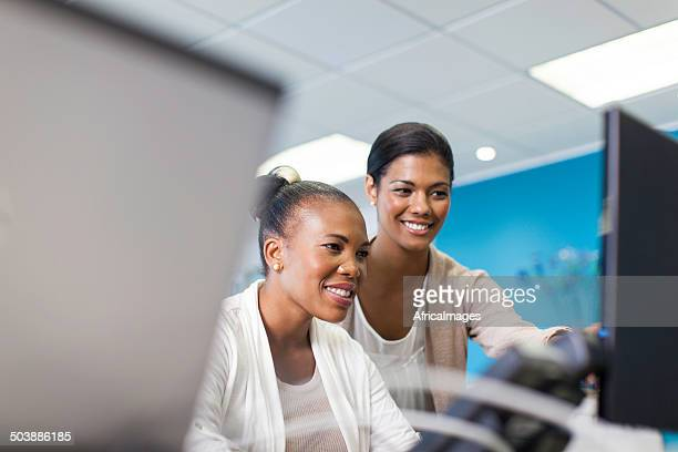 African businesswoman helping her colleague.