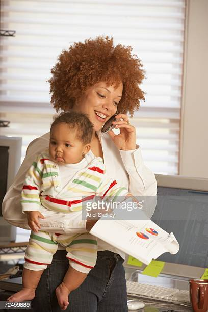 african businesswoman holding baby and using cell phone - black ginger baby stock photos and pictures