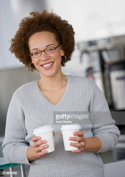 African businesswoman holding take out coffees