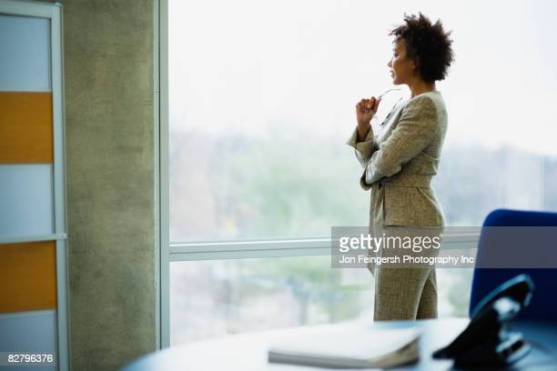 African businesswoman looking out window in office