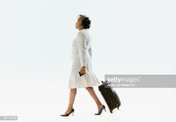 African businesswoman pulling suitcase