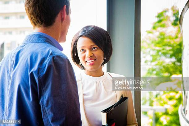 African businesswoman smiles at Caucasian male colleague