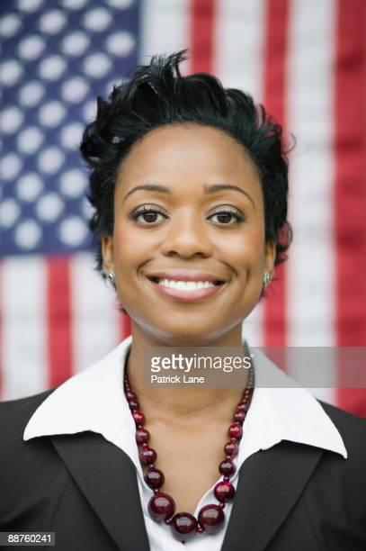 African businesswoman standing near American flag